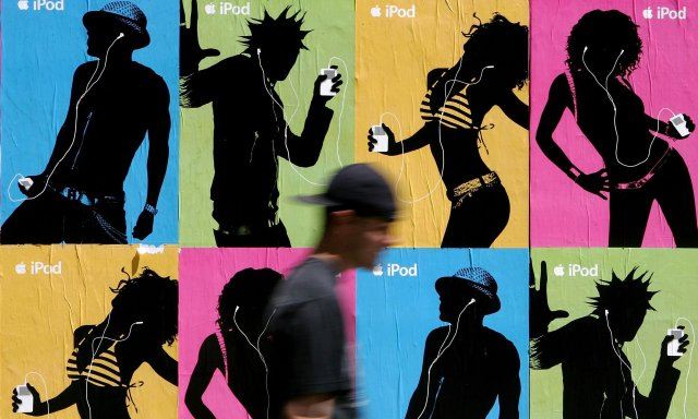 A pedestrian passes a wall covered with Apple iPod advertisements in 2005.