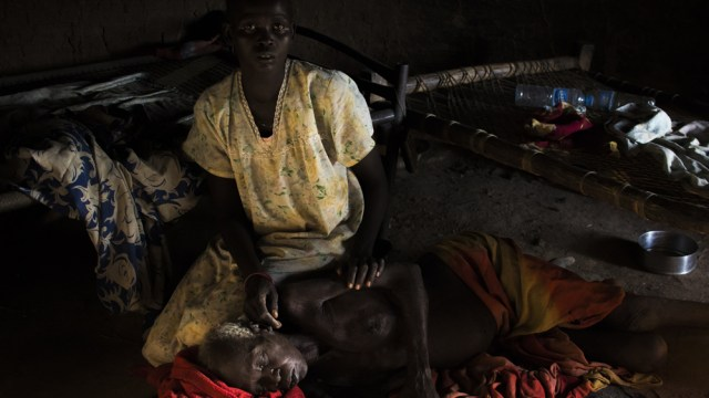 Abang Akok lies on the floor of her family home as one of her daughters brushes flies from her