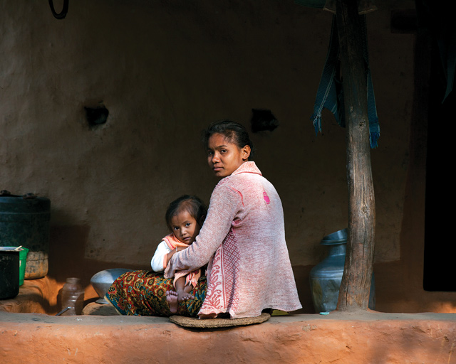 Man Kumari Tamang, 24, with her daughter Srijana, 4. Srijana has a congenital heart problem, and when Man Kumari is not taking care of her she is fetching water up from the river.