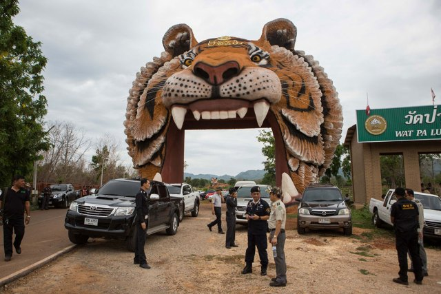 Department of National Parks, Wildlife and Plant Conservation [DNP] officers surround the entrance of the Tiger Temple grounds as they await for a court order to enter the grounds and remove the tigers.