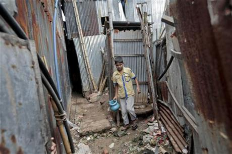 In this June 1, 2016 photo, a Bangladeshi boy walks out from a toilet at a slum in Dhaka, Bangladesh. Through a dogged campaign to build toilets and educate Bangladeshis about the dangers of open defecation, the densely populated South Asian nation has managed to reduce the number of people who defecate in the open to just 1 percent of the 166 million population, according to the government, down from 43 percent in 2003.