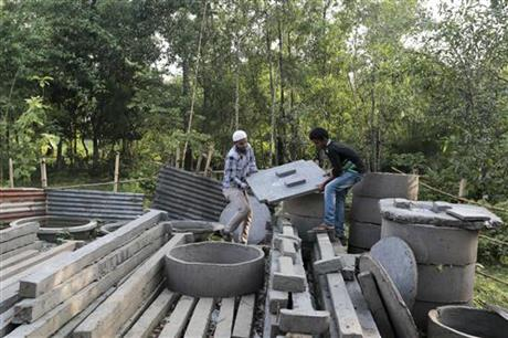 In this May 30, 2016 photo, Bangladeshi volunteers, working to spread awareness on sanitation, lift toilet seats in Bormi village, near Dhaka, Bangladesh. Bangladesh's success in sanitation, something so far unattained by India, came from a dogged campaign supported by 25 percent of the country's overall development budget.