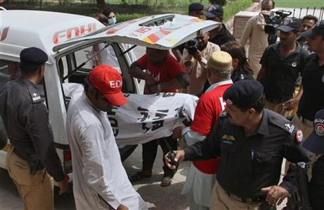 Pakistani police officers stand beside volunteers unloading the dead body of fashion model Qandeel Baloch upon arrival at a local hospital in Multan, Pakistan, July 16, 2016. Baloch, who recently stirred controversy by posting pictures of herself with a Muslim cleric on social media, was strangled to death by her brother, police said Saturday, July 16, 2016.