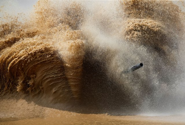 A tank's barrel is seen through the spray on the course of the Tank Biathlon competition in Alabino, outside of Moscow.