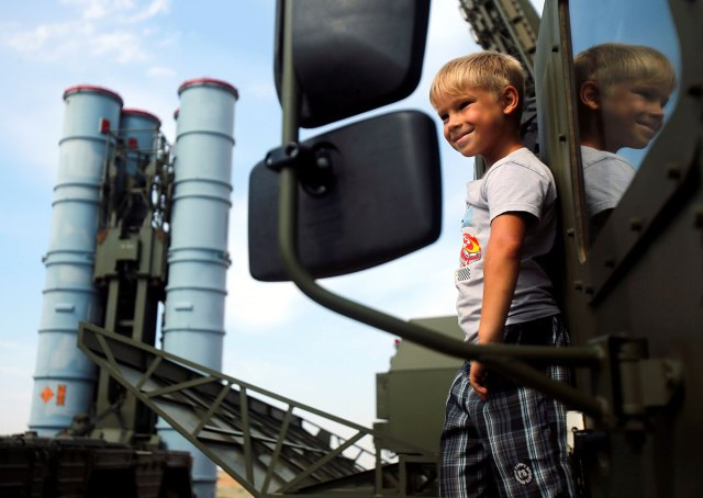 A boy stands on the S-300 air defence mobile missile system during the International Army Games 2016 at the Ashuluk military polygon outside of Astrakhan, Russia.