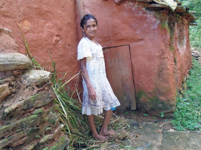 Sangita stands beside the chhaugoth (shed for menstruating women) near her home. Its door is almost half her size, and she has to stay here every month when she menstruates. (Sabita)
