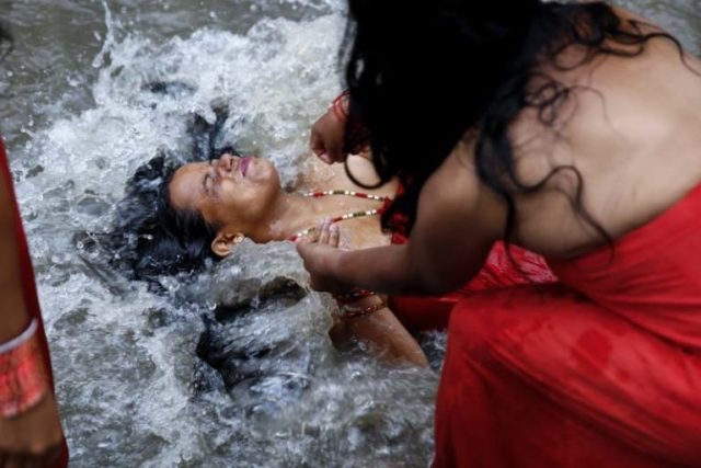 A Nepalese Hindu woman dips in the Bagmati River inside Pashupathinath Temple premise, a UNESCO World Heritage Site in Kathmandu, Nepal on Tuesday, September 6, 16. Rishi Panchami is observed to mark the end of three-day Teej festival when women worship Sapta Rishi (Seven Saints) on the last day to wash off one's impurity for the whole year.