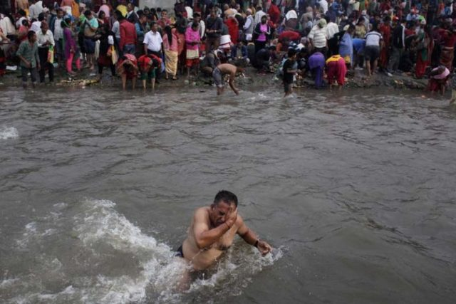 A Nepalese devotee takes a holy dip in Bagmati river during Kuse Aunsi in Gokarneshwar Hindu temple, Kathmandu, Nepal, Thursday, Sept. 1, 2016. Kuse Aunsi is a Hindu festival of Nepal where fathers, living or dead, are honored. Children with living fathers show their appreciation by giving presents and sweets and those whose fathers are deceased pay tributes at Gokarneshwar temple. (AP Photo/Niranjan Shrestha)