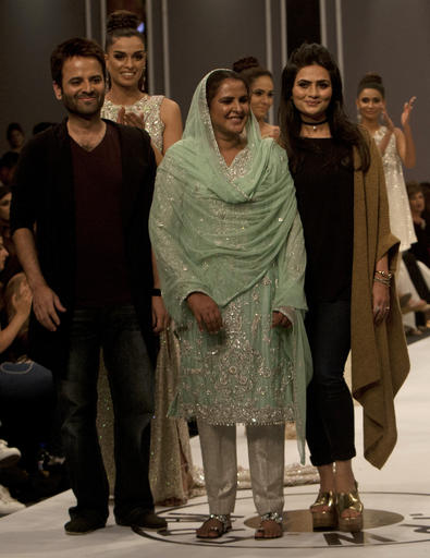 Pakistan's gang rape victim Mukhtar Mai, centre, walks with models during a fashion show in Karachi, Pakistan, Tuesday, Nov. 1, 2016. Gang-raped and paraded naked 14 years ago, Mukhtar Mai walked on a ramp in Pakistan fashion week on Tuesday. A red-carpet reception accorded in Pakistani southern city of Karachi by country's elite fashionista is her debut appearance, which she says she's doing as a symbol of courage for womenfolk. (AP Photo/Shakil Adil)
