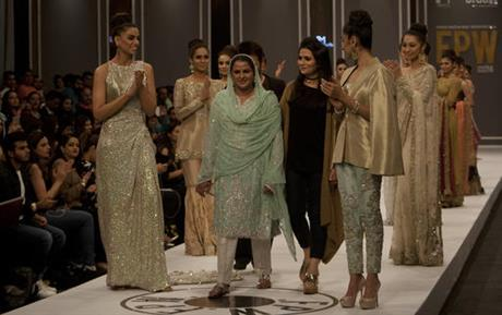 Pakistan's gang rape victim Mukhtar Mai, centre, walks with models during a fashion show in Karachi, Pakistan, Tuesday, Nov. 1, 2016. Gang-raped and paraded naked 14 years ago, Mukhtar Mai walked on a ramp in Pakistan fashion week on Tuesday. A red-carpet reception accorded in Pakistani southern city of Karachi by country's elite fashionista is her debut appearance, which she says she's doing as a symbol of courage for womenfolk.