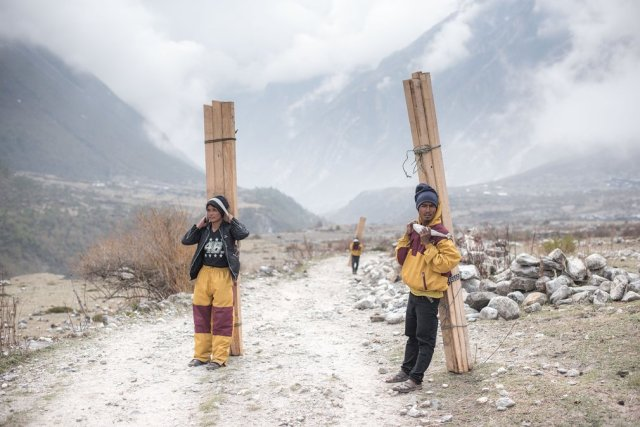 With few other forms of transport available – the cost of helicopters is prohibitive – teams involved in rebuilding the mountain villages have to walk for three days up the valley, hauling heavy loads of wood