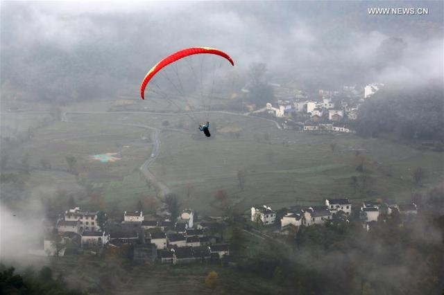 A person flies a glider over the Tachuan Village of Yixian County in Huangshan City, east China's Anhui Province, Nov. 19, 2016