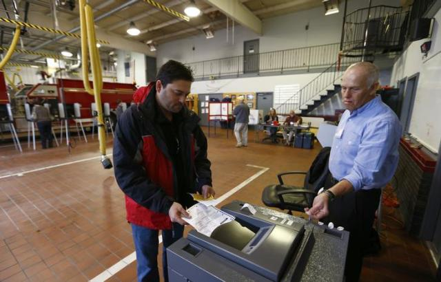 Voter Troy Brewer (L) casts his paper ballot by inserting it into a machine that scans the ballots as poll worker Robert Carrick (R) looks on at the Providence Volunteer Fire Department during the U.S. presidential election in Matthews, North Carolina November 6, 2012. REUTERS/Chris Keane (UNITED STATES - Tags: POLITICS USA PRESIDENTIAL ELECTION ELECTIONS)