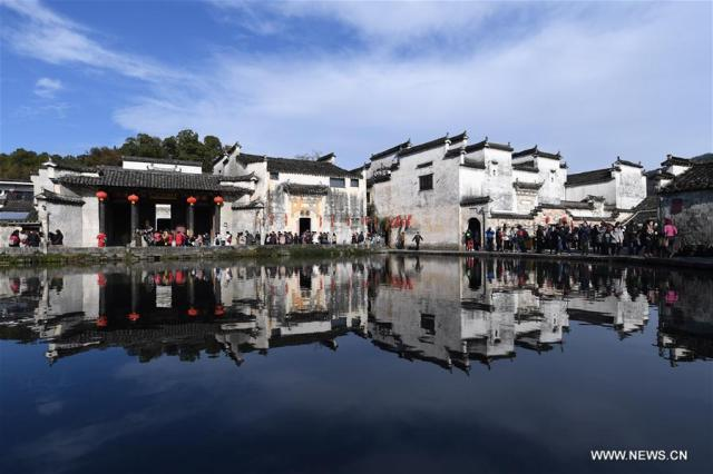 People visit the Yuezhao, or Moon Pool, at Hongcun, an ancient village in Yixian County in Huangshan City, east China's Anhui Province, Nov. 26, 2016.