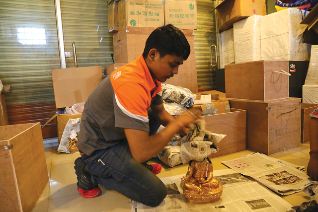 TRANSBOUNDARY E-COMMERCE: A worker wraps a Buddha statue before being shipped to China.