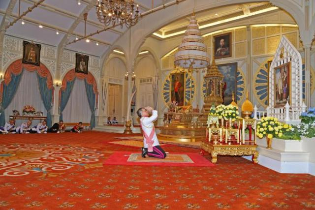 Thailand's new King Maha Vajiralongkorn Bodindradebayavarangkun pays respect to a picture of Thailand's late King Bhumibol Addlyadej and Queen Sirikit, as he accepts an invitation from parliament to succeed his father, at Bangkok's Dusit Palace in Bangkok, Thailand, December 1, 2016. Thailand Royal Household Bureau/Handout via REUTERS.