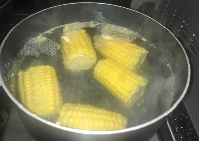 Corn on the cob boiling in a pan.