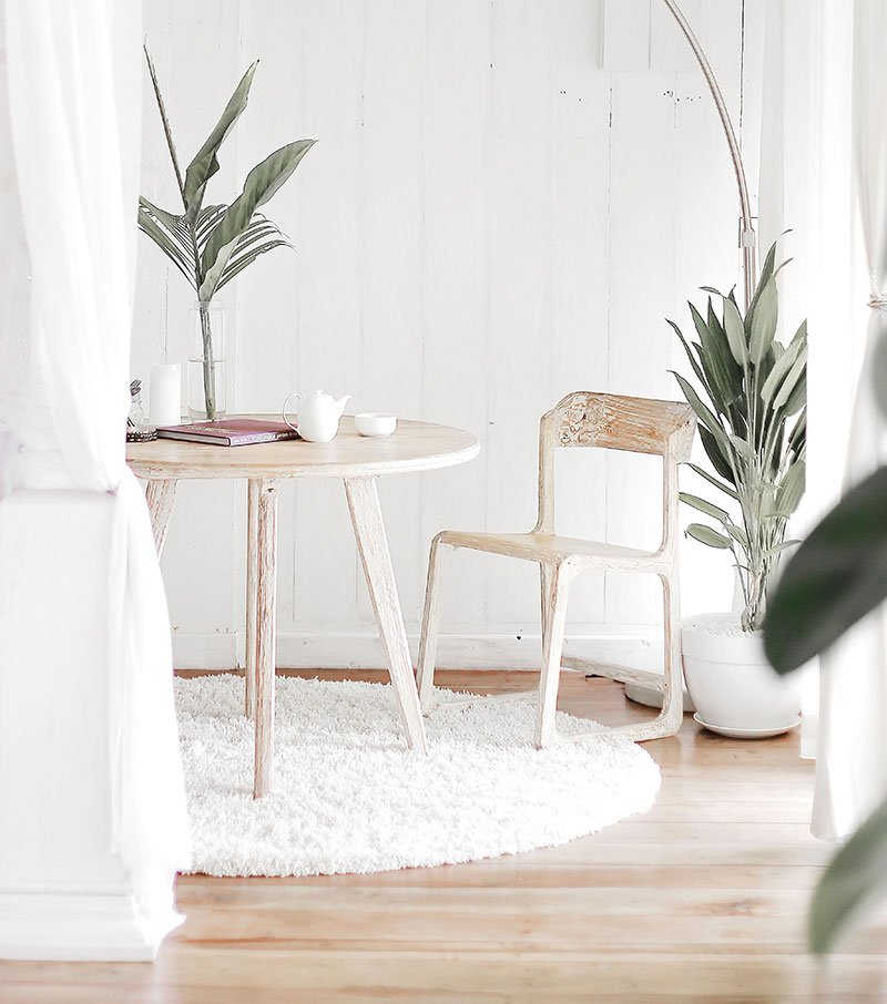 beige room with green plants in dining room