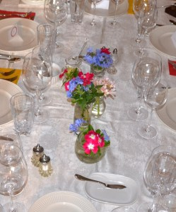 The blooms from the garden brighten the lovely crystal and linen backdrop