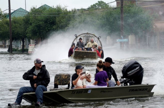 People are rescued from flood waters from Hurricane Harvey on an air boat in Dickinson