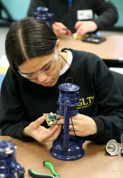 GLTS sophomore Caroline Anziani, of Lawrence, from the electrical shop, solders a circuit, which will be used to connect the battery of the solar light. (Courtesy Photo GLTS)