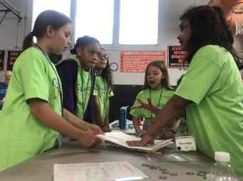 Elementary school students on the black team discuss how to best build a bridge that could withstand added weight pulling down on its middle. Left to right: Charlee Annarelli, Kiara Montilla, Leilani Guzman, Sydney Klein and Dhruvisha Shukla. (Courtesy Photo GLTS)