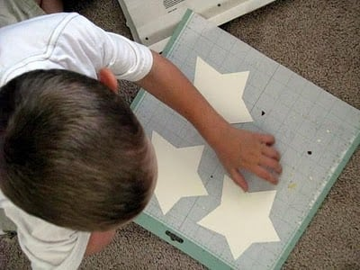 child peeling star cut outs off of cutting mat
