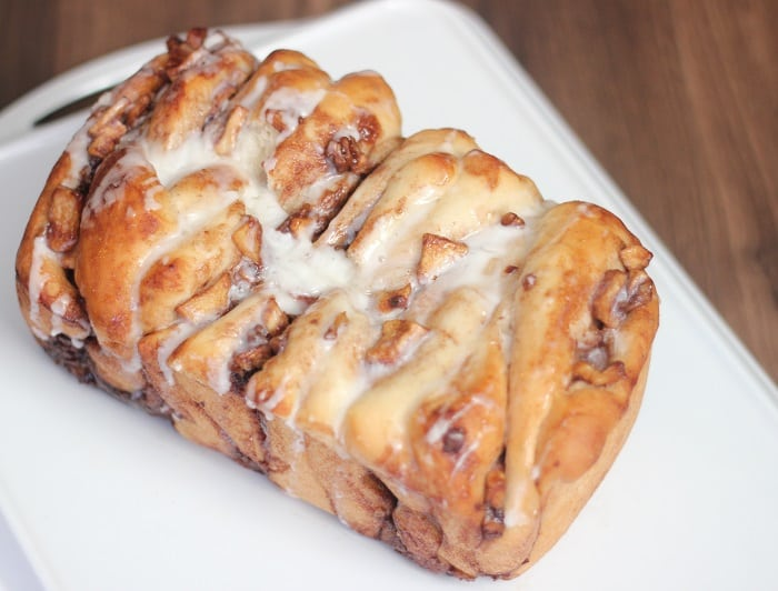 This apple cinnamon pull apart bread is a delicious light, pull apart bread with diced apples, a buttery cinnamon filling, chopped walnuts. Drizzled with a sugary glaze it's a family tradition for us--- make it one for yours too.
