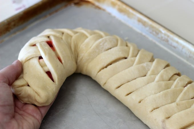 This delicious cherry filled candy cane braided bread is drizzled witha sweet vanilla icing! It's the perfect treat for the holidays.