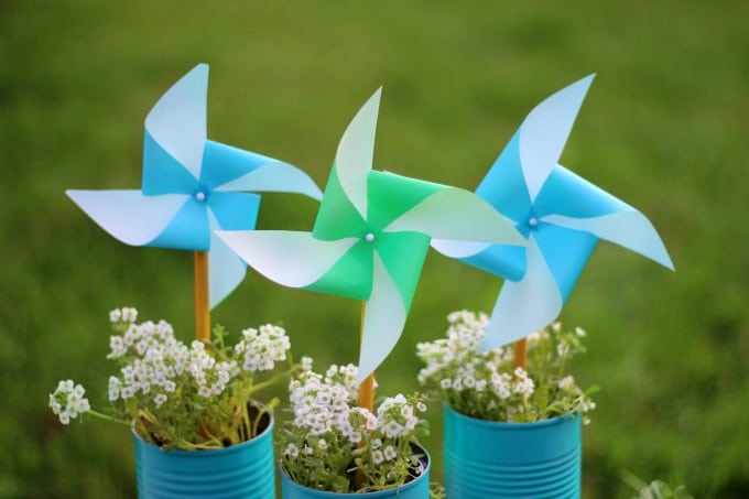 A fun earth day craft for the kids to make this year! These pinwheels come together fast and spin in the wind even faster! We used recycled tin cans, added 3 coats of spray paint and turned them into the perfect planters for our flowers and a way to display our pinwheels!