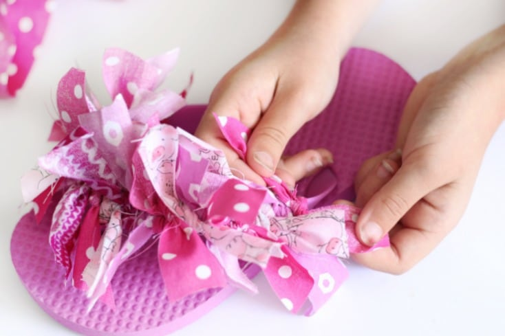 """Decorate flip flops with scrap fabric to make these fun and funky """"Fluffy Flip Flops"""". A quick and easy summer camp project for girls and a great way to use up fabric scraps. Create patterns or tie the strips on randomly, the choice is yours!"""