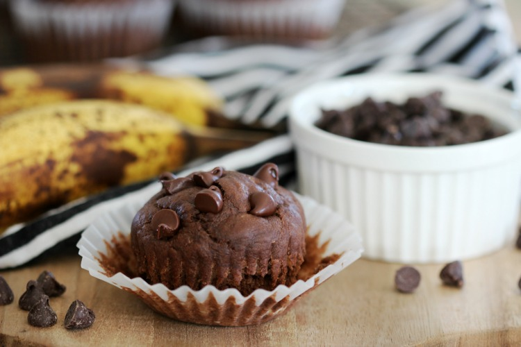 chocolate banana muffin on cutting board next to bowl of chocolate chips
