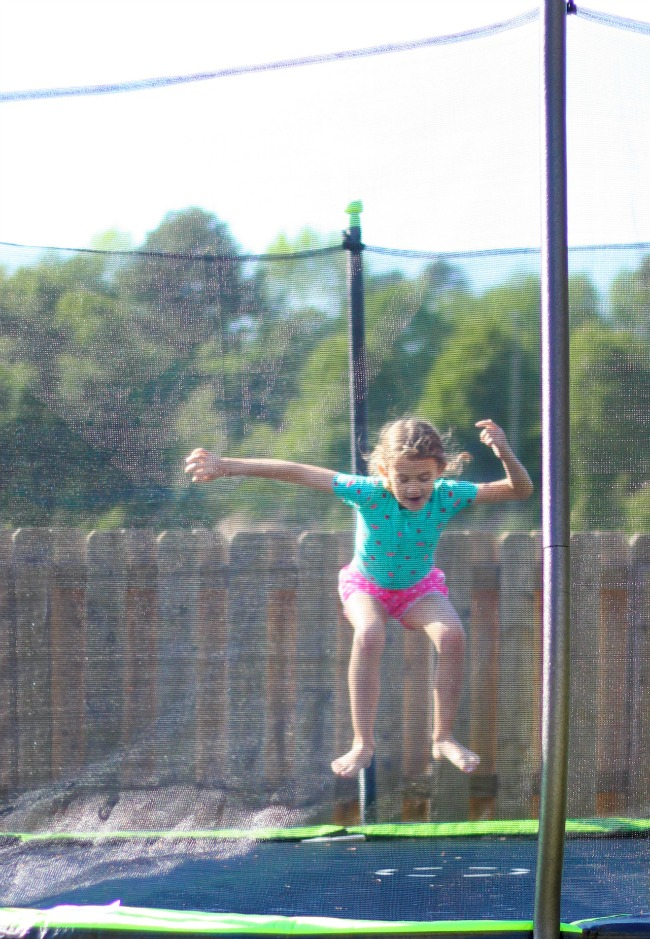 backyard activities for kids: girl jumping on trampoline