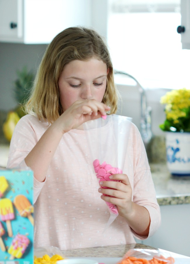child filling frosting bag with candy melts