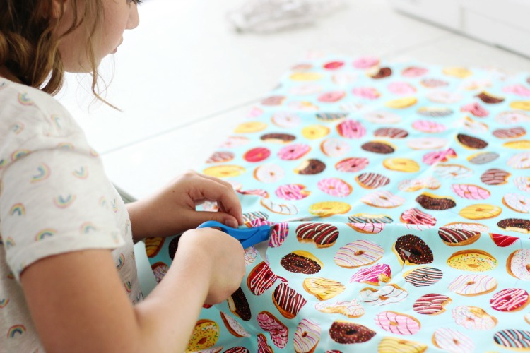 girl cutting out circle on fabric