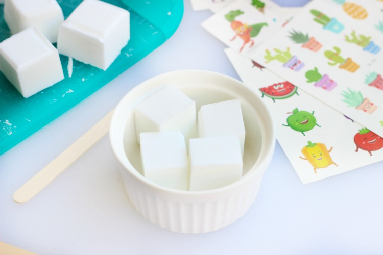 4 cubes of melting blocks in bowl with popsicle stick and temporary tattoos on table