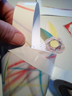 Applying double stick tape to secure the (flowers) over the staples