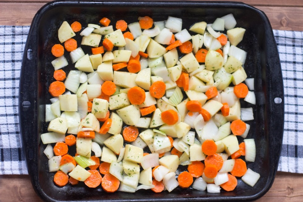 Potatoes, onions, and carrots in a roasting pan