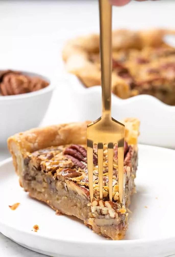 Gabel wird in ein Stück gf-Pekannusstorte auf einem kleinen weißen Teller mit einer kleinen Schüssel Pekannüsse und dem Rest des Kuchens im Hintergrund eingefügt