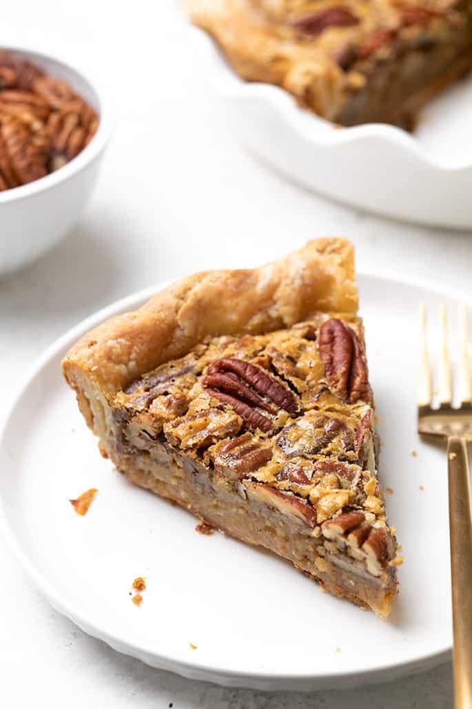 Stück glutenfreie Pekannuss-Torte auf kleinem weißen Teller mit Rest Torte im Hintergrund in weißer Tortenplatte und kleiner weißer Schüssel mit Pekannüssen