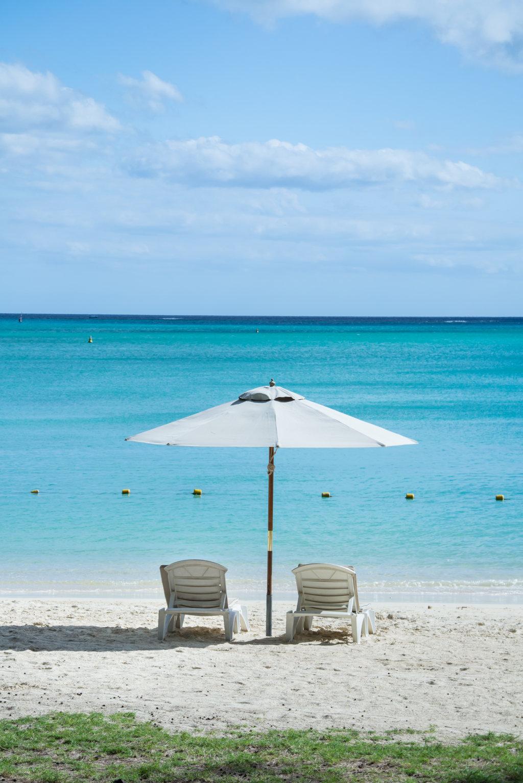Sonnenstühle und Sonnenschirm am Strand auf Mauritius