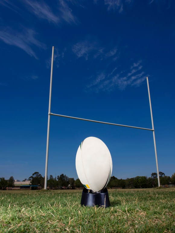 Rugby ball in front of goal posts
