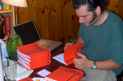 Joshua A.C. Newman signs and numbers the pre-ordered copies of Shock: Social Science Fiction