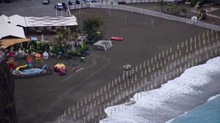 Beach umbrellas on a black sandy beach