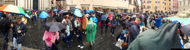A sea of raincoats and umbrellas