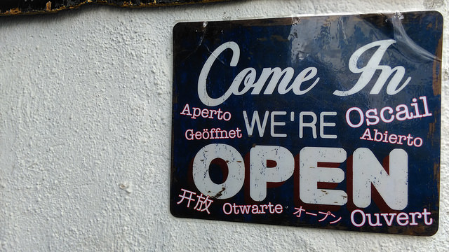 Sign reading 'Come in, we are open' in many languages