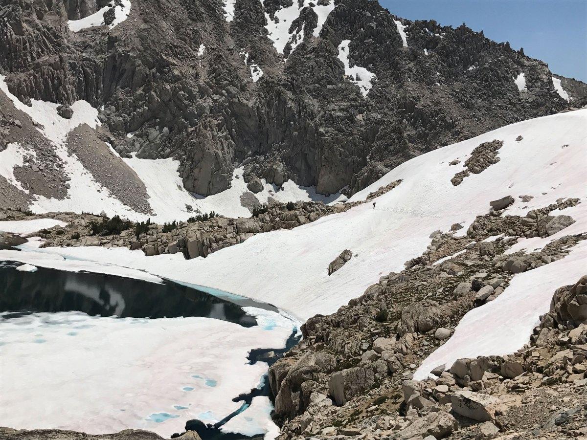Backpacking the John Muir Trail (JMT). A hiker traverses snow approaching Glen Pass