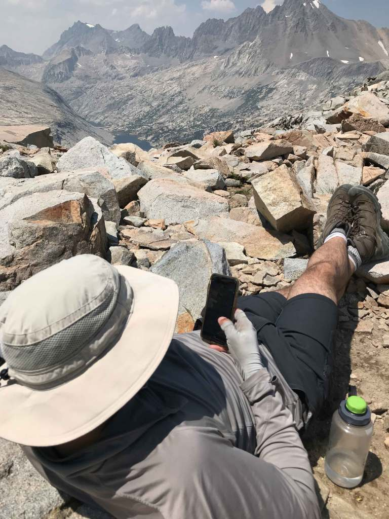My husband Joe resting on top of Mather Pass. There is no cell signal on top of this pass, I have no idea what he's looking at on his phone.