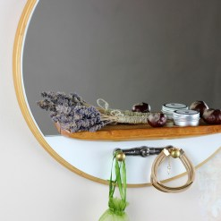 Round wall mirror with rustic wood shelf and vintage hooks