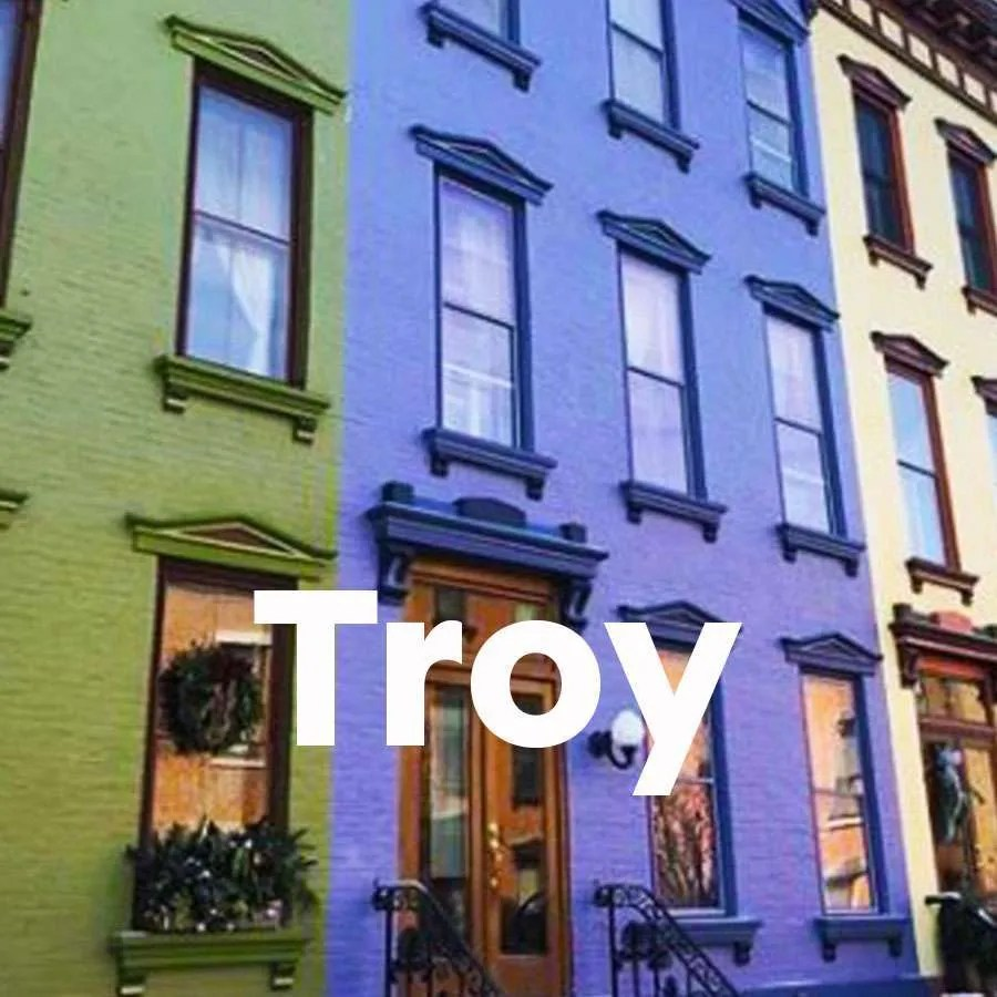 """Photo of brightly colored brownstones with a super across the photo that says """"Troy"""""""